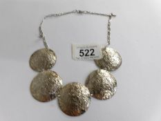 A textured solid silver necklace as round discs.