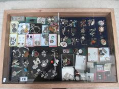A display case containing in excess of 100 pieces of mainly silver jewellery including earrings,
