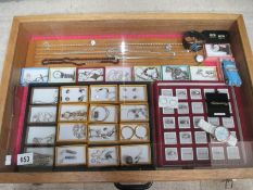 A display case containing silver rings, silver chains, other jewellery and watches etc.