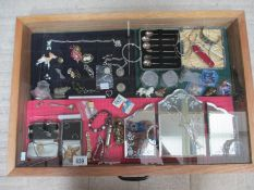 A display case containing a mixed lot of jewellery including some silver, a cased set of spoons etc.