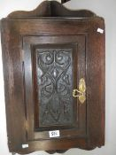 """An early 20th century carved oak corner cupboard, 30"""" tall."""