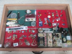 A display case containing assorted jewellery, trinket boxes, badges etc.