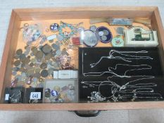 A display case containing assorted coins, silver pendants and other jewellery etc.
