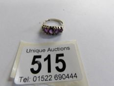 A mid 20th century five stone amethyst set ring in 9ct gold, size M.