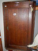 An old oak wall hanging corner cupboard.