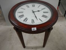 An occasional table with clock inset to top.