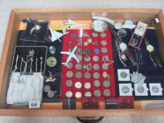 A display case containing silver chains, assorted coins, model aircraft, watches, cloth badges etc.