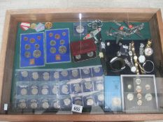 A display case containing miscellaneous coins, watches, medals etc.