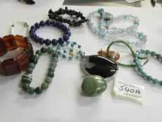 A mixed lot of stone pendants and bracelets.