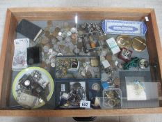 A display case containing assorted coins, bank notes, jewellery, powder compacts etc.