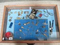 A display case of miscellaneous items including watches, jewellery, Wade Whimsies etc.