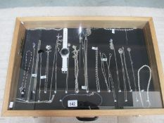 A display case of mainly silver pendants, bracelets and chains, (this lot is buyer collect only).
