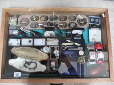 A display case containing assorted jewellery, watches, model cars etc.