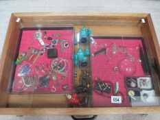 A display case containing miscellaneous badges, jewellery etc., (this lot is buyer collect only).