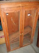 A Pine wall cabinet with glass door.
