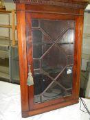A mahogany astragal glazed hanging corner cabinet.