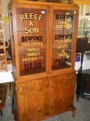 An Edwardian walnut veneered advertising display cabinet.