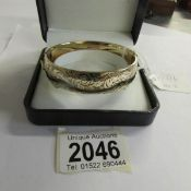 A circa 1970/80's, 9ct gold on a metal engraved bangle.