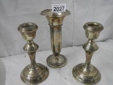 A pair of silver candlesticks and a silver spill vase.