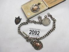A silver watch chain and 4 silver fobs, 83 grams / 2.9 ounces.