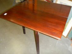 A fold over card table on square mahogany legs.
