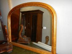 A gilded arched top overmantel mirror.