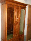 A satin walnut wardrobe with double mirrored doors.