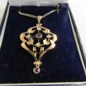 An early 20th century garnet and pearl set pendant stamped 9ct gold with attached silver chain.