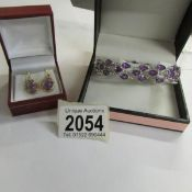 A pair of amethyst set ear pendants in yellow metal together with an amethyst set bracelet with