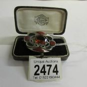 A Scottish brooch set with coloured agate stones in silver,