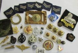 A mixed lot of military badges, buttons etc.