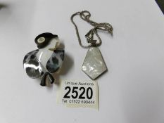 A Lucite lady brooch and a silver pendant.
