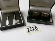 A pair of silver amber cuff links and a pair of silver pendant earrings.
