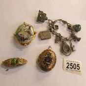 A Yellow metal pendant, 2 brooches and a charm bracelet.