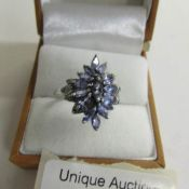A tanzanite and diamond ring cluster setting in silver, size O.