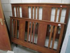 An inlaid castored wood bedframe with metal siderails