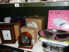 2 shelves of kitchen ware and 4 good boxed unused battery clocks.