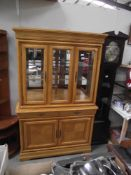 A light wood display cabinet with cupboard base