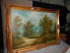 A gilt framed oil on canvas woodland scene.