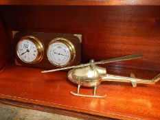 A solid brass helicopter and a ships style clock barometer.