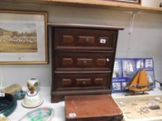 A dark wood bedside chest