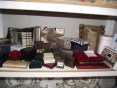 A shelf of empty jewellery boxes, small cushions, bow tie and cufflinks, watch,