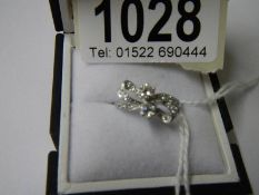 An 18ct white gold and diamond bow ring, size K.