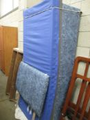 A mottled blue single bed base with matching head board and protected mattress