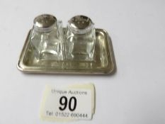 A silver topped salt & pepper on silver tray.