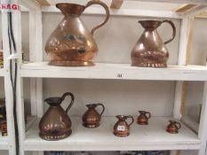 A set of seven graduated copper ale jugs