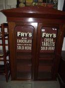 A 2 door display cabinet with Frys Chocolate advertising to doors