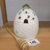 A Belleek honey pot decorated with shamrocks and bees.