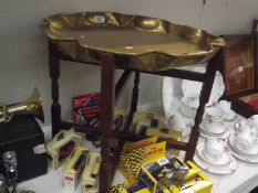 An Eastern brass tray table with folding base.