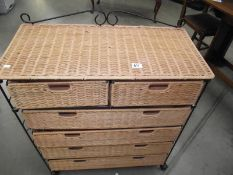 A wicker and wrought iron bathroom chest of drawers.